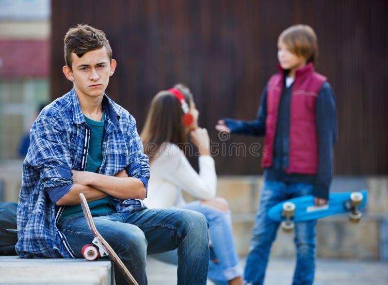 Ragazzo turbato e coppie degli anni dell'adolescenza a parte sulla via fotografia stock