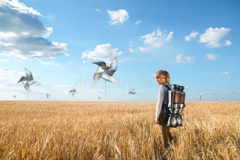 Ragazzo in un campo con le eliche fotografia stock