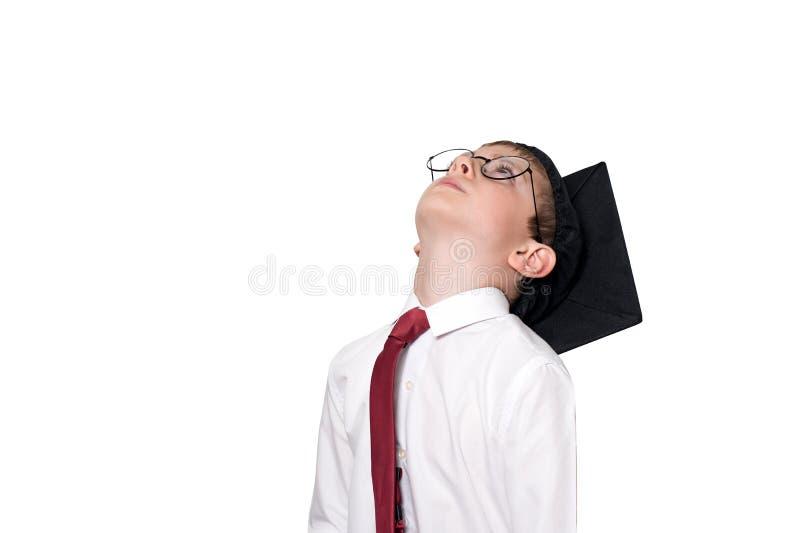 Ragazzo in un lookong accademico quadrato di vetro e del cappello su Concetto del banco isolato fotografie stock libere da diritti