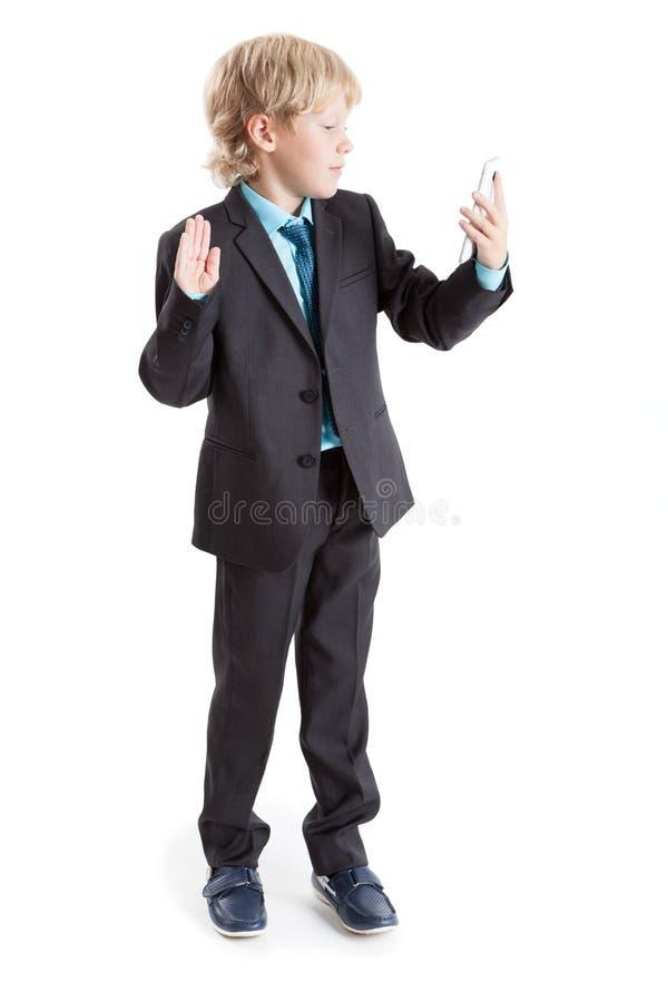 Ragazzo in un vestito che ondeggia al telefono cellulare della macchina fotografica, fondo bianco isolato immagine stock
