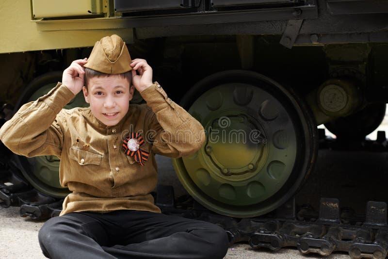 Ragazzo vestito in uniforme militare sovietica durante la seconda guerra mondiale che posa vicino al carro armato di esercito immagine stock