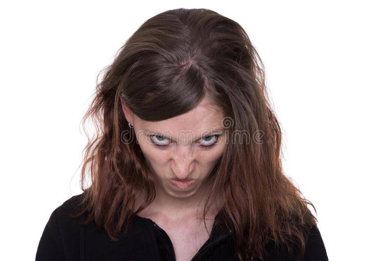 Rage. Young long haired woman looks furious at the camera royalty free stock photo