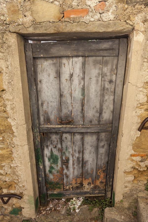 Ragged καφετιά ξύλινη πόρτα σε μια κινηματογράφηση σε πρώτο πλάνο τοίχων πετρών του του χωριού σπιτιού Ιταλία στοκ εικόνες