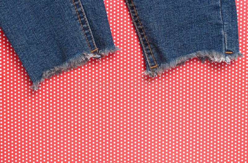 Ragged jeans on red creative backgroundin polka dot. Top view. royalty free stock image