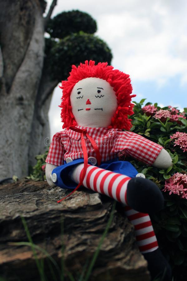 Raggedy Anne doll sitting outside, Old Time Rag Doll, Ghost mystic doll. Scary horror doll. Raggedy Anne doll sitting outside, Old Time Rag Doll, Ghost mystic stock image