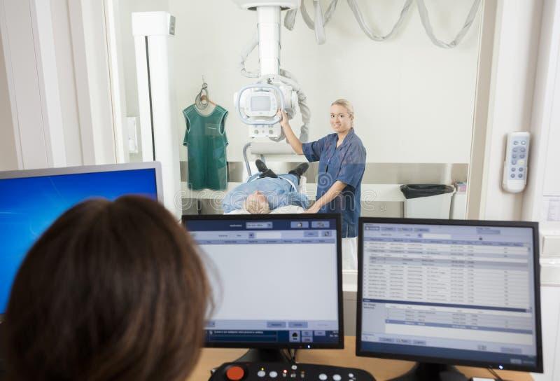 Raggi x del ` s di Taking Patient del radiologo mentre collega che per mezzo del computer immagini stock libere da diritti