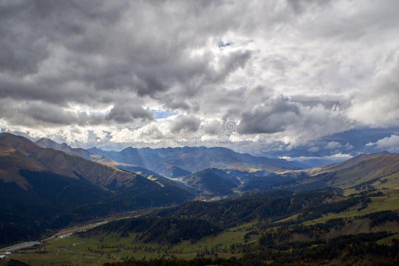 Raggi del sole attraverso il cielo tempestoso sopra una valle della montagna fotografia stock