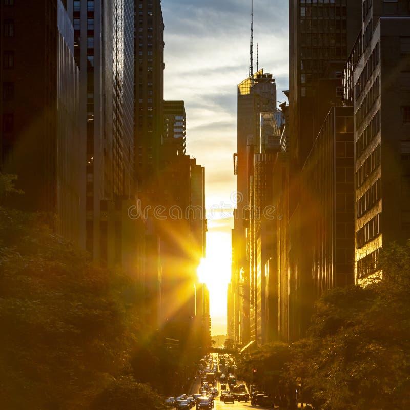 Raggi di luce solare che splendono fra le costruzioni dell'orizzonte lungo la quarantaduesima via nel Midtown Manhattan, New York immagine stock libera da diritti