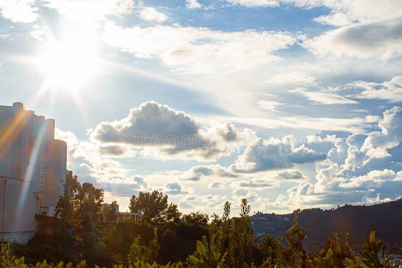 Raggi di sole da luce solare, da sunflare sopra le piante del pendio di collina e dalle case del pendio di collina immagini stock libere da diritti