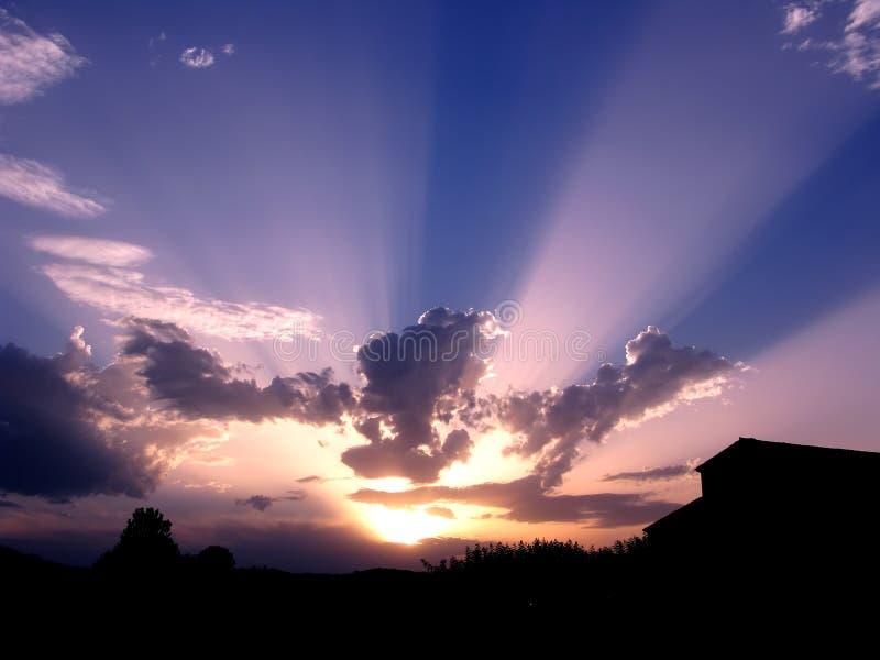 Raggi di Sun fra le nubi, al crepuscolo immagine stock libera da diritti