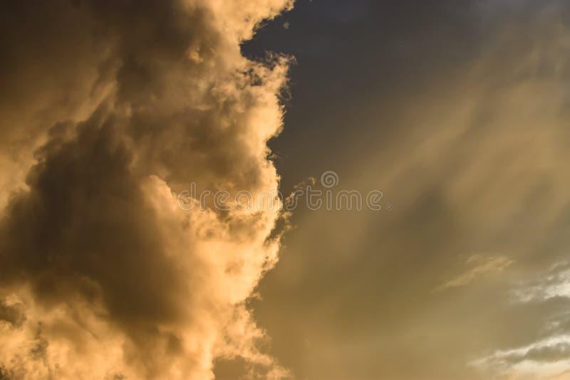 raggi dorati nelle nuvole e nel cielo, quando il sole mette immagine stock libera da diritti