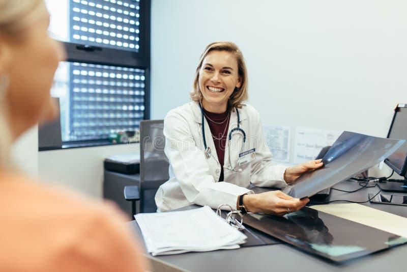 Raggi x sorridenti della tenuta di medico che comunicano con il paziente immagini stock libere da diritti