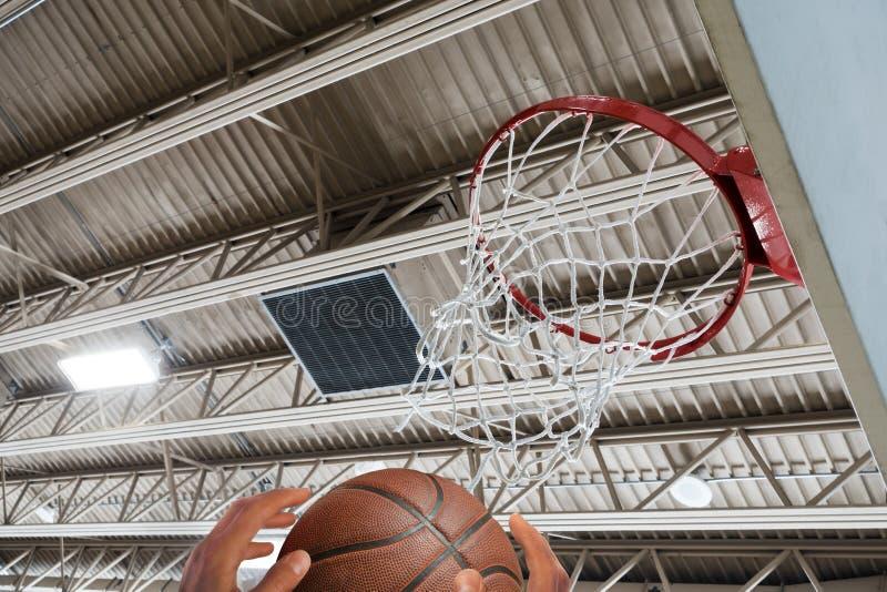Raggiungendo per la pallacanestro sotto il cerchio immagini stock libere da diritti