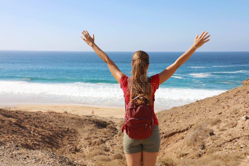 Raggiungere l'obiettivo Il backpacker donna escursionista arriva nell'Oceano Atlantico dopo un lungo viaggio e festeggia con le b fotografia stock