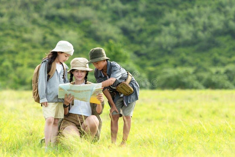 Raggruppa bambini asiatici che controllano la mappa nell'avventura della giungla e il turismo per viaggi di destinazione e di sva fotografia stock libera da diritti