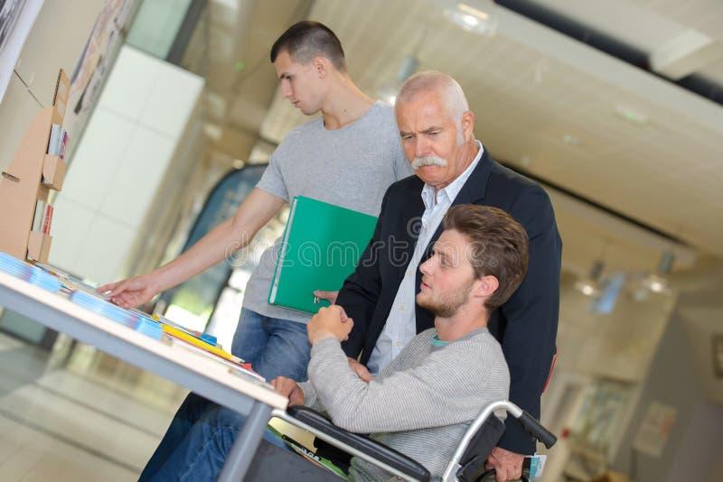 Raggruppi gli studenti adulti attenti con l'insegnante maschio in aula immagine stock
