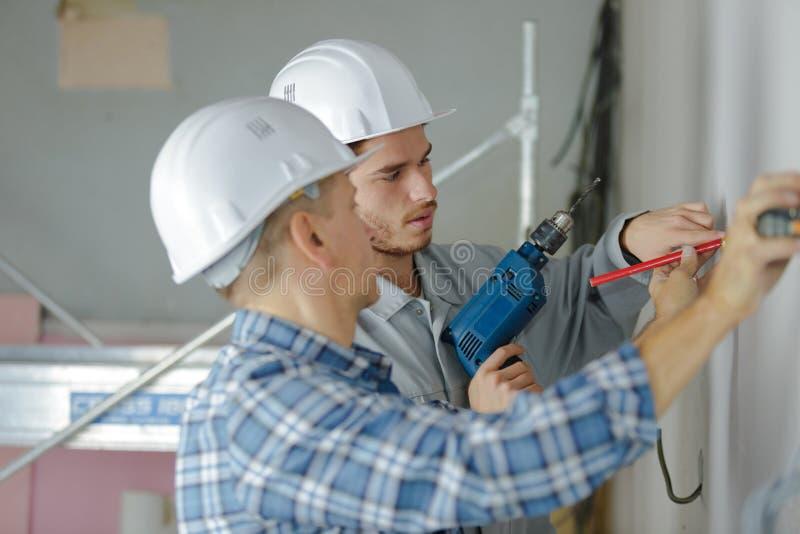 Raggruppi i costruttori in elmetti protettivi con il trapano elettrico all'interno fotografia stock