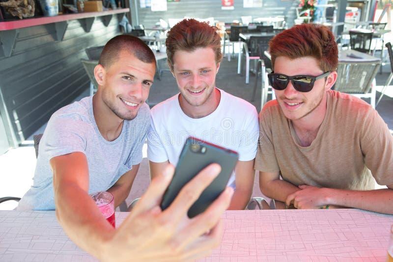 Raggruppi i giovani amici turistici che prendono il selfie alla barra fotografia stock libera da diritti