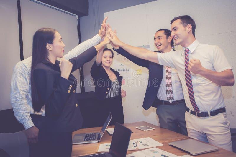 Raggruppi il gruppo asiatico della gente di affari con il gesto di successo che dà ciao cinque nella riunione, accordo fotografia stock libera da diritti