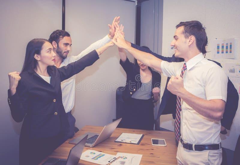 Raggruppi il gruppo asiatico della gente di affari con il gesto di successo che dà ciao cinque nella riunione, accordo fotografie stock libere da diritti