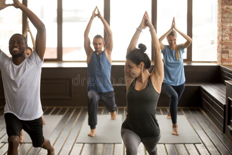 Raggruppi l'yoga in studio, diversa gente che fa gli esercizi con il instru immagine stock