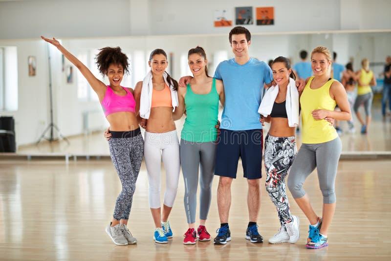 Raggruppi la foto della gente sportiva sorridente sulla classe di forma fisica immagine stock libera da diritti