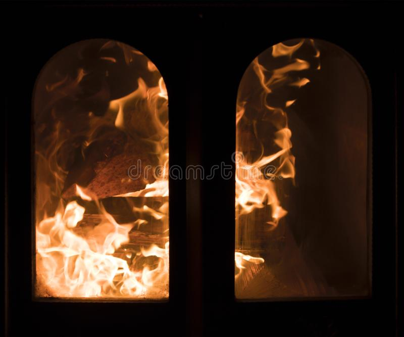 Raging forks of flame in fireplace. Behind the protective glass screen stock photo