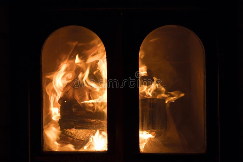 Raging forks of flame in fireplace. Behind the protective glass screen royalty free stock photography