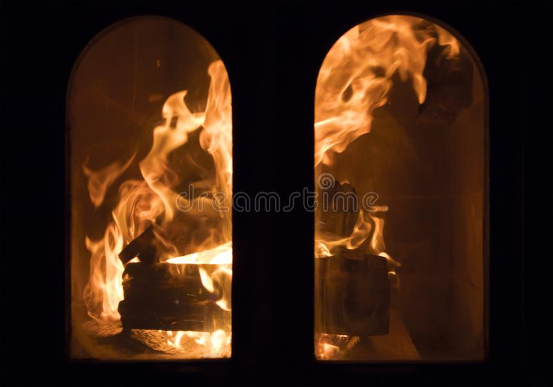 Raging forks of flame in fireplace. Behind the protective glass screen stock photos
