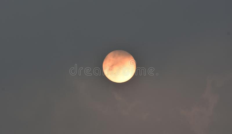 Raging sun. Rising sun with cloudy background, saffron, yellow stock photography