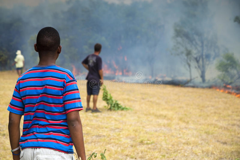 Raging wildfire in Port Elizabeth, South Africa. Adults and children keeping a wildfire under control that is raging near a home for destitute adults and a royalty free stock photos