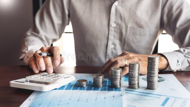 Ragioniere Calculating dell'uomo d'affari sui documenti di dati e sulla pila di monete, l'investimento del mucchio dei soldi di r fotografia stock