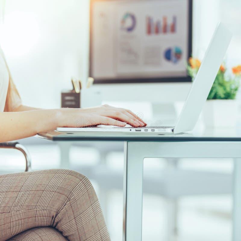 Ragioniere che lavora ad un computer portatile con i grafici finanziari sullo scrittorio fotografia stock