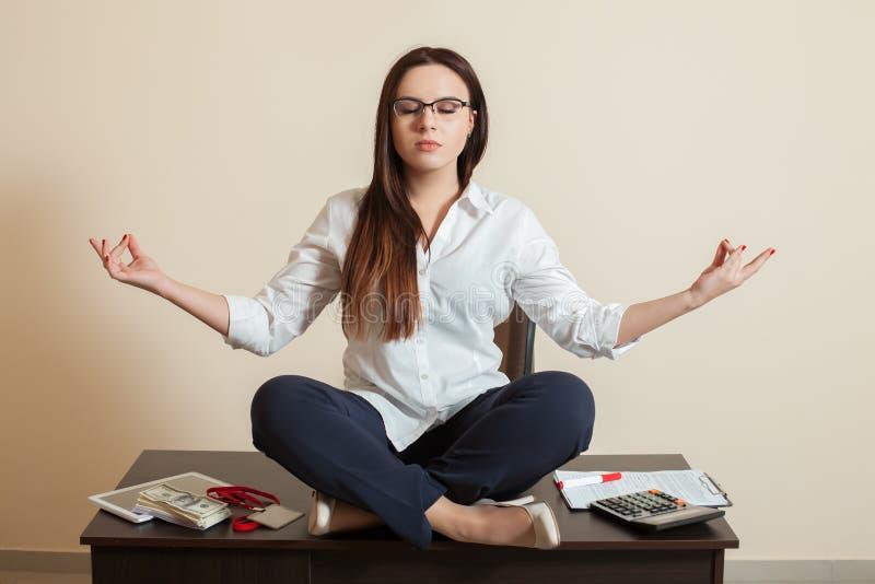 Ragioniere che si siede nella posa di yoga sulla tavola fotografia stock