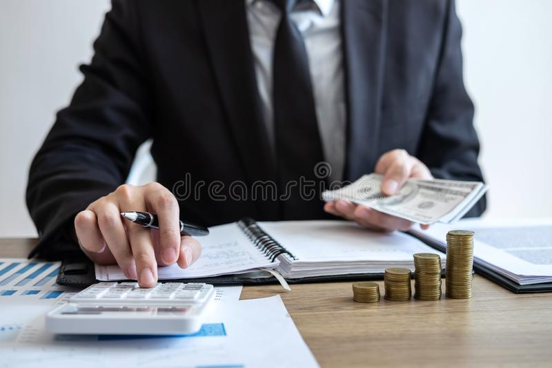 Ragioniere dell'uomo d'affari che conta soldi e che fa le note al rapporto che fa le finanze e calcolare circa costo dell'investi immagini stock