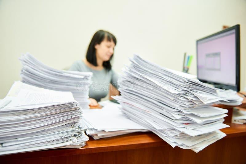 Ragioniere della lavoratrice con i lotti dei documenti cartacei fotografie stock