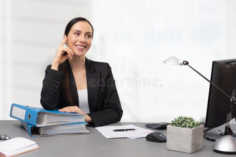 Ragioniere femminile che si siede allo scrittorio in ufficio fotografia stock