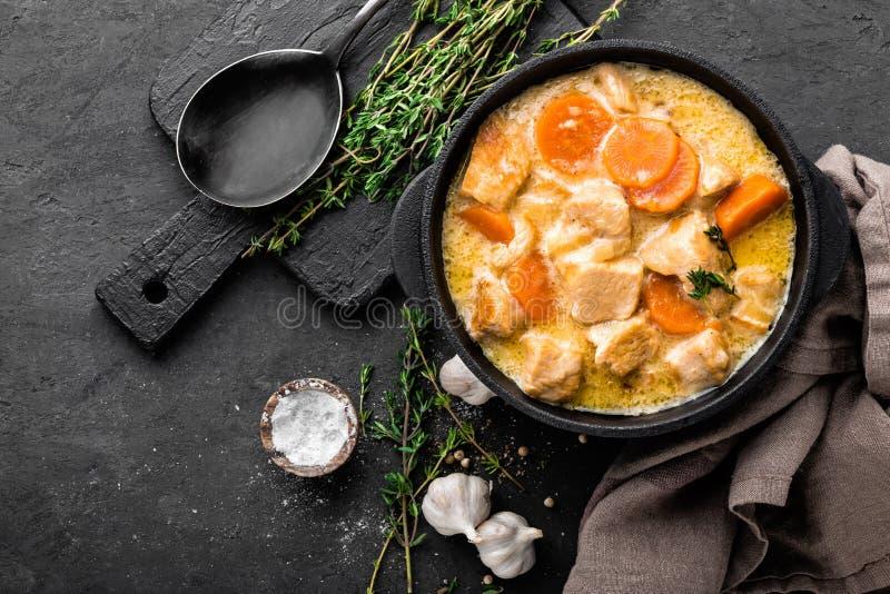 Ragoût de viande, filet de poulet en sauce avec la carotte dans un pot de fonte photo stock