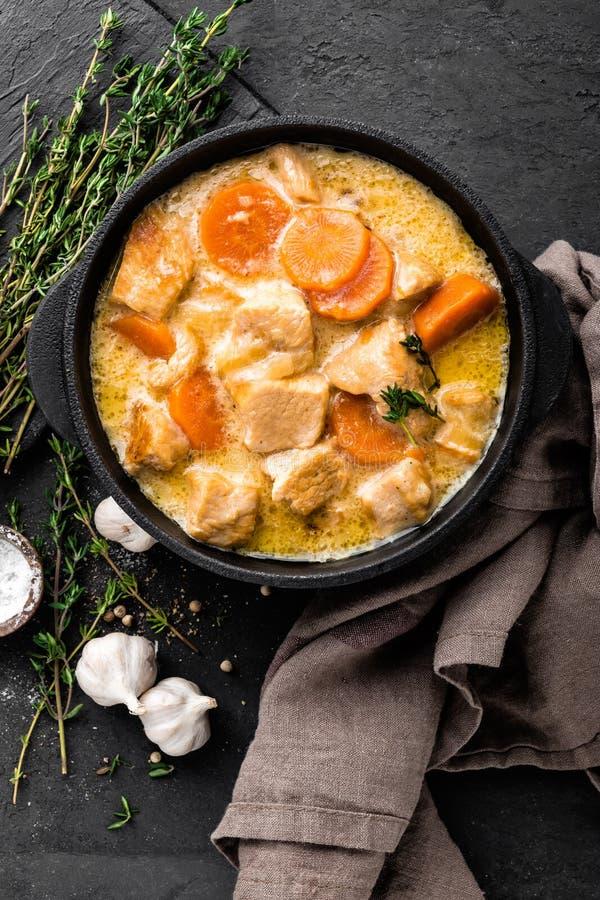 Ragoût de viande, filet de poulet en sauce avec la carotte dans un pot de fonte photos libres de droits