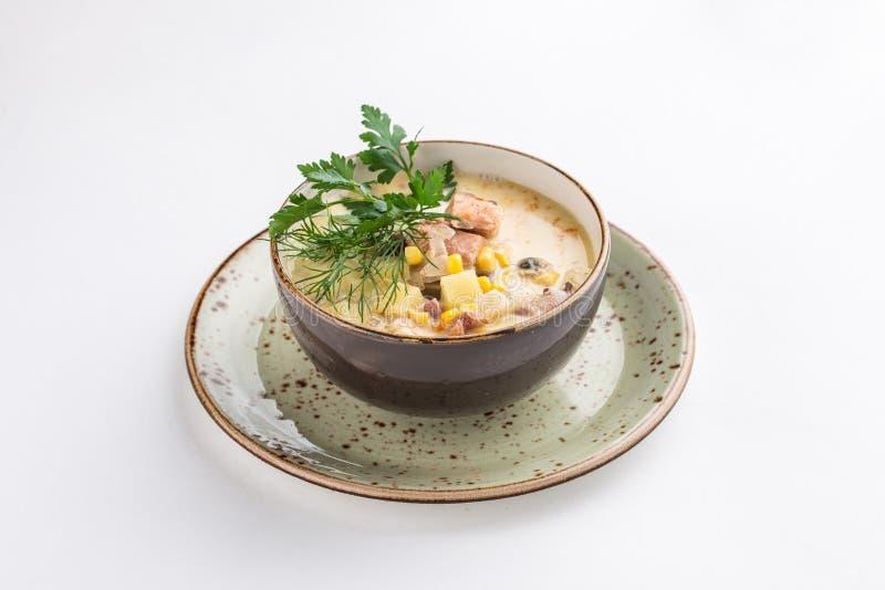 Ragout avec des saumons, des pommes de terre et le maïs dans la cuvette en céramique d'isolement sur le fond blanc images libres de droits