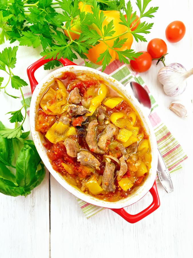 Ragout of meat and vegetables in red brazier on board top. Ragout of turkey meat, tomato, yellow sweet pepper and onion with sauce in a brazier on a towel on the royalty free stock image