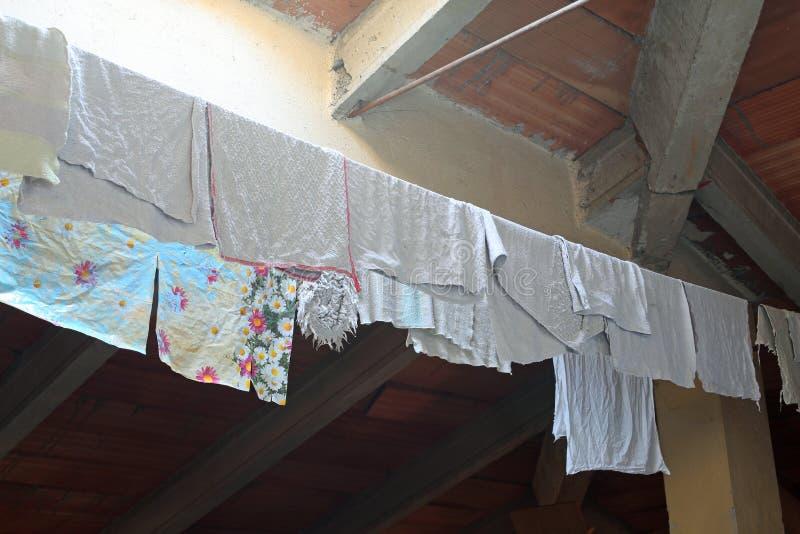 Rags et canovars humides ont accroché pour sécher dans le grenier de la maison photo stock