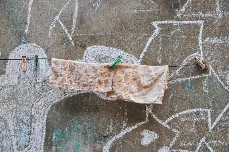 Rags hanging on a line of old wall royalty free stock photography