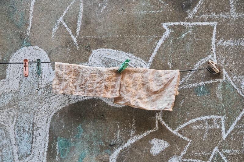 Rags som hänger på en linje av den gamla väggen royaltyfri fotografi