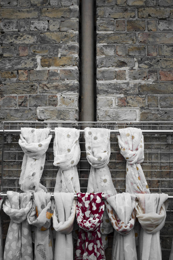 Rags tied up on poles in front of brick wall stock image