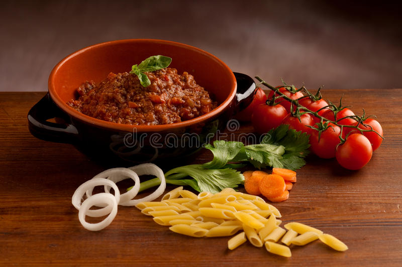 Ragu in bowl and raw macaroni royalty free stock image