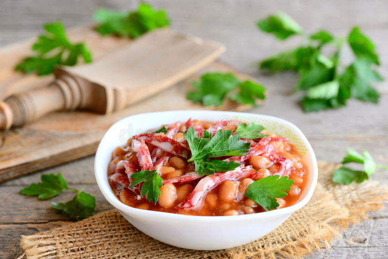Ragu för röd böna med rökte korvskivor, tomatsås och ny persilja i en bunke och på en trätappningtabell arkivbild