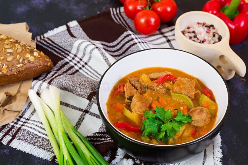 Ragu med kött och grönsaker i tomatsås på mörk bakgrund arkivbilder