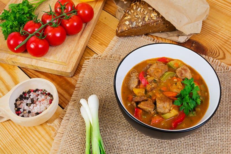 Ragu med kött och grönsaker i tomatsås på träbakgrund royaltyfri fotografi