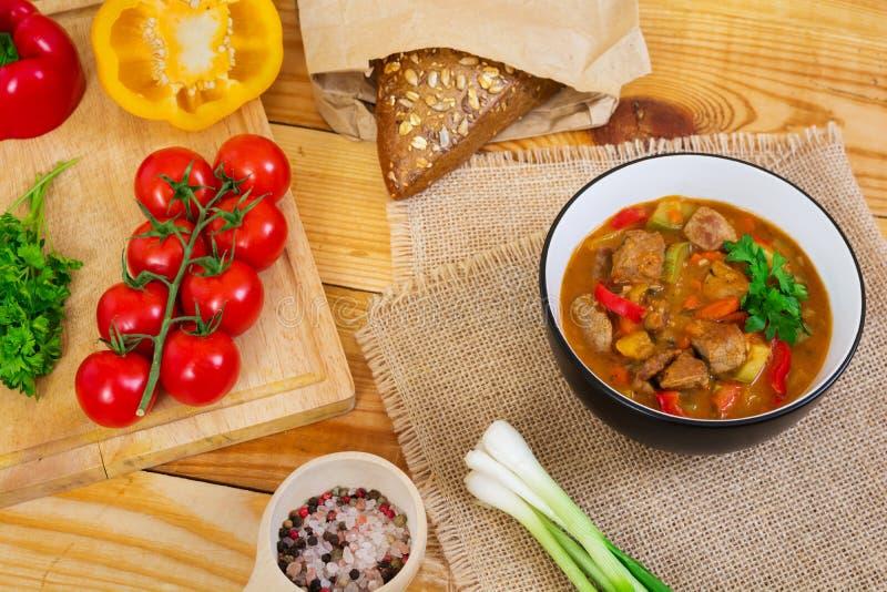 Ragu med kött och grönsaker i tomatsås på träbakgrund arkivfoto
